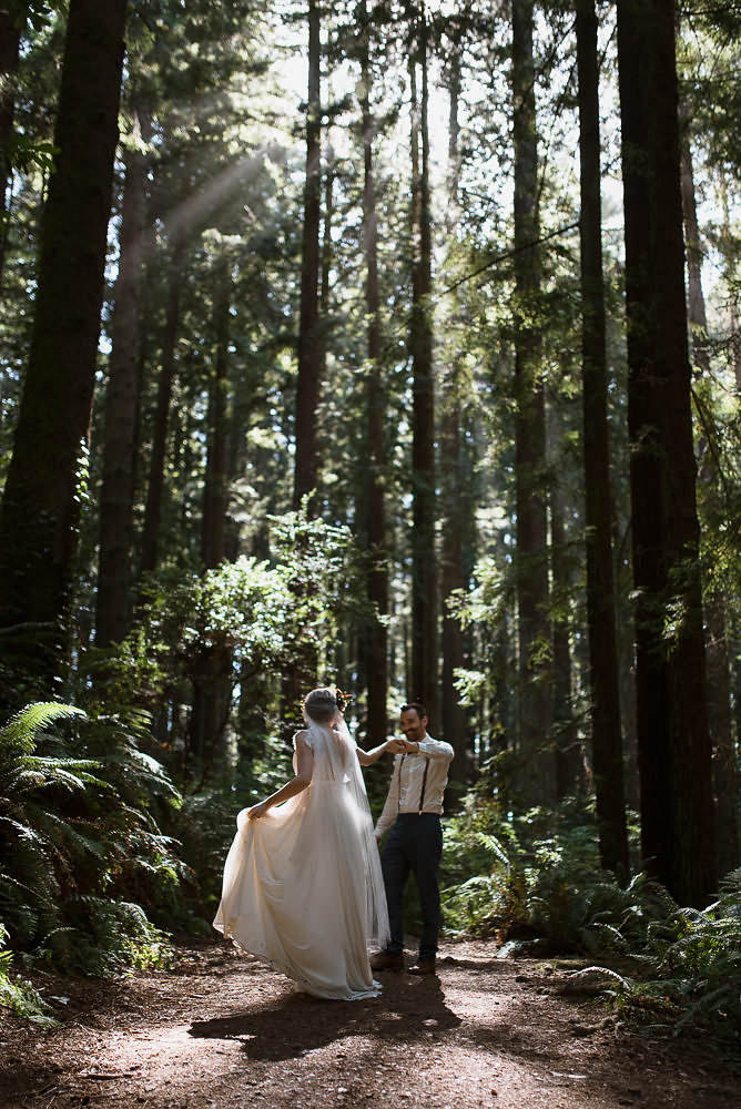 Bride and groom dancing in the redwood forest in California