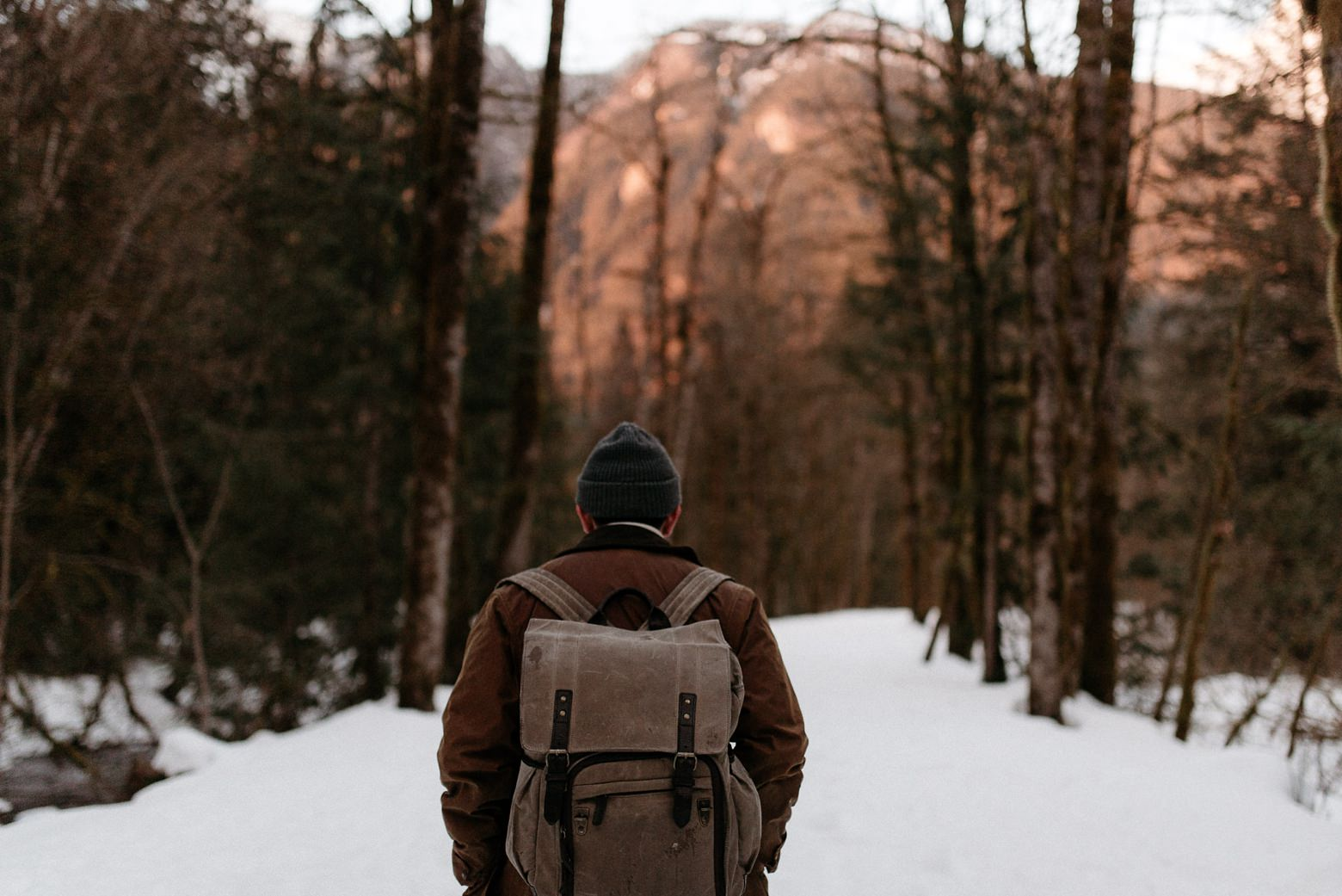 photographer walking on the snow ONA backpack