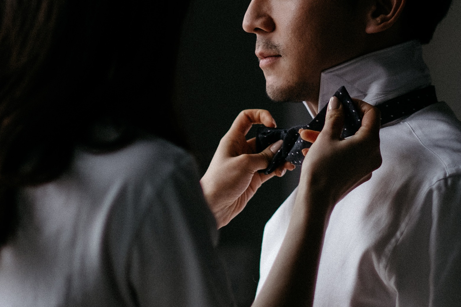 bride making bowtie on groom