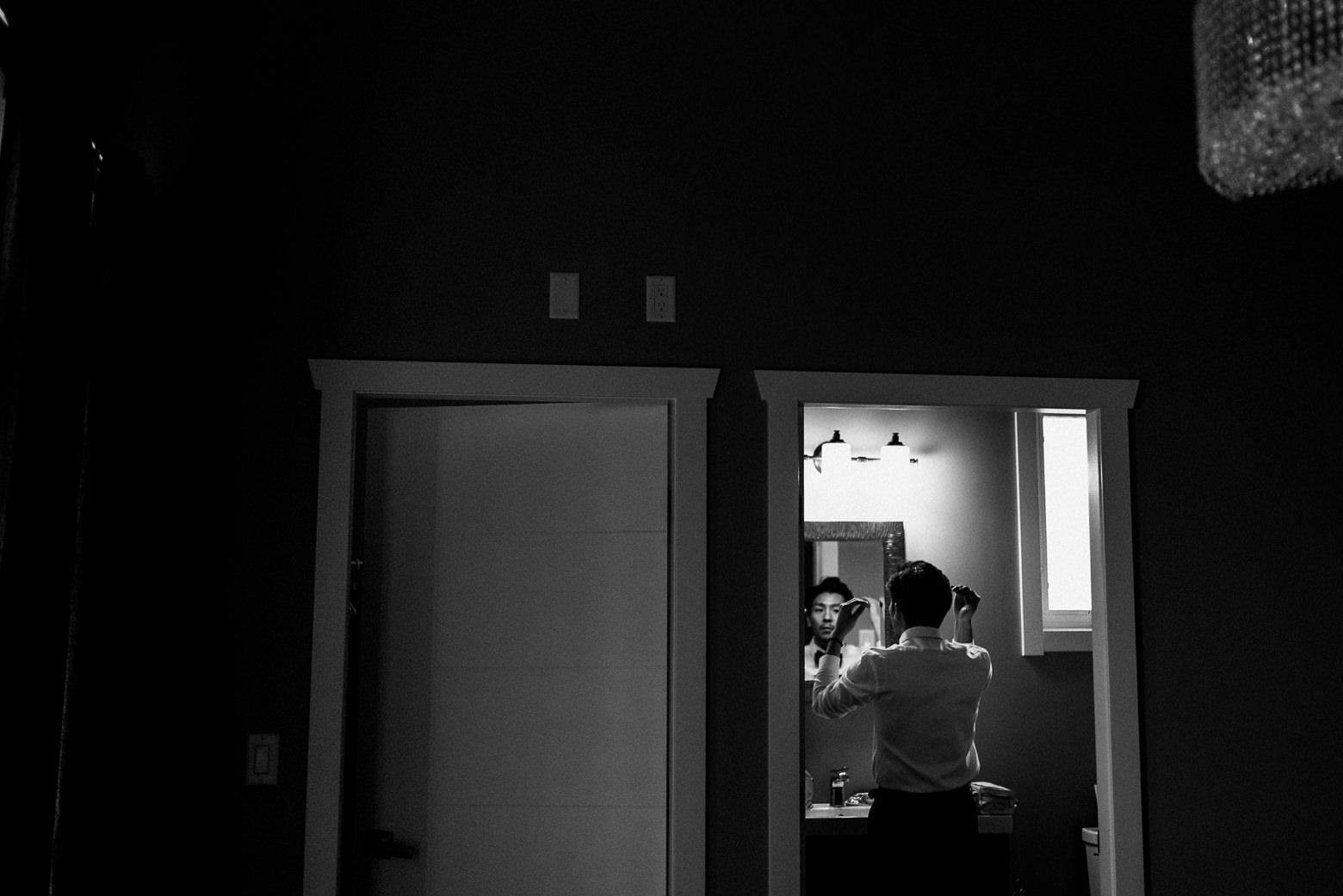 groom getting ready window reflection